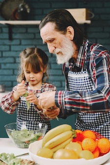 Mature couple and their granddaughter preparing food