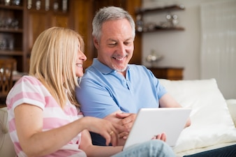 Mature couple using a digital tablet in their apartment