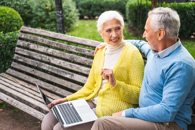 Mature couple using computer laptop on a bench