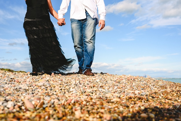 Mature couple walking on the beach by the hand of day