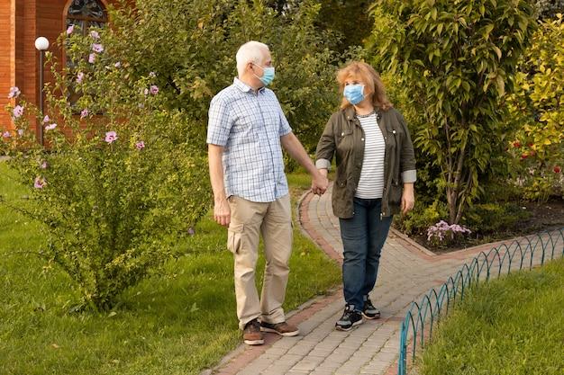医療マスクを身に着けている春または夏の公園を歩く成熟したカップル