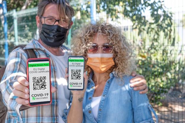 Covid19のワクチン接種のデジタル証明書付きの携帯電話を保持しているサージカルマスクを身に着けている成熟したカップル-電話に焦点を当てる