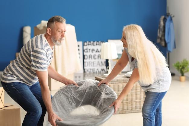 Пожилая пара с креслом в комнате после переезда в новый дом