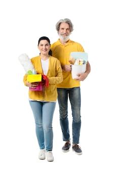 흰색 표면에 청소 용품으로 성숙한 부부