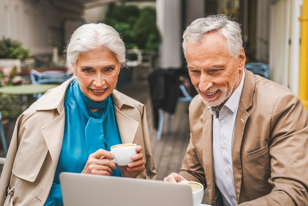 Mature couple with laptop computer sitting in a restaurant