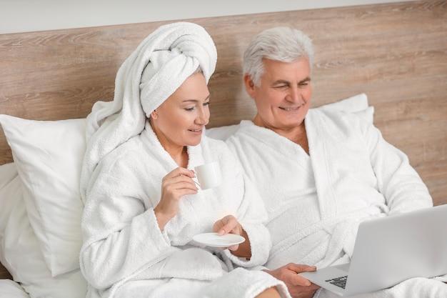Пожилая пара с ноутбуком, отдыхая на кровати