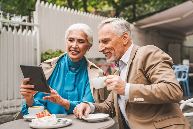 Mature couple with tablet sitting in a restaurant