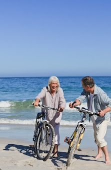 Mature couple with their bikes on the beach