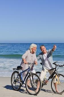 해변에서 자전거와 함께 성숙한 부부