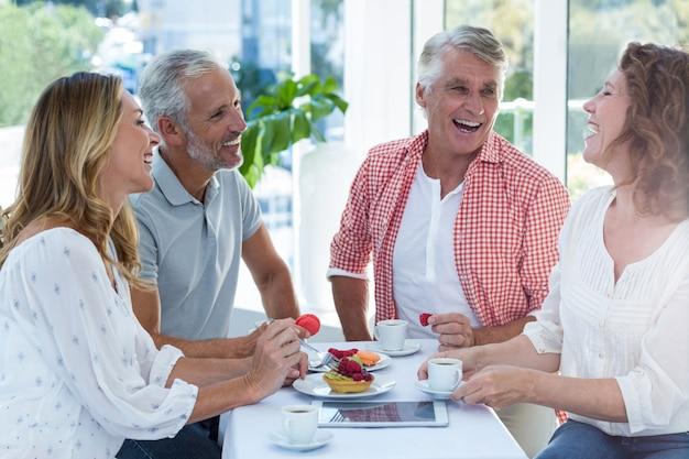 Пожилые пары, имеющие еду в ресторане