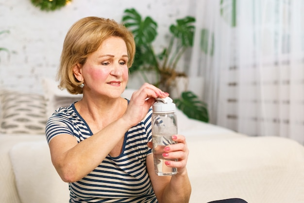 Mature cute tired woman after sports workout drinks water from a bottle at home