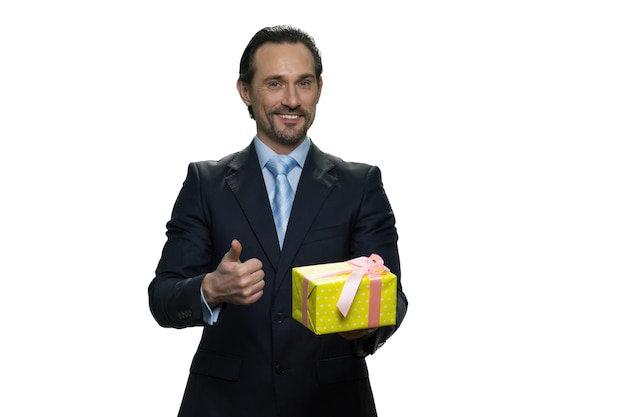 선물을 들고 소송에서 성숙한 감독입니다. 행복 한 사업가 선물이 있습니다. 흰 벽에 고립 된 쾌활 한 공식적인 옷을 입은 남자.