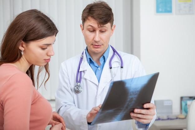 의료 약속 동안 그의 여성 환자의 엑스레이 스캔을 검사하는 성숙한 의사