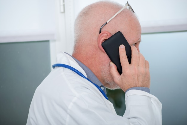 Mature doctor on phone in his office