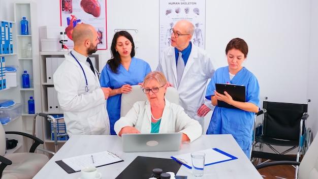 성숙한 의사 전문가가 노트북을 사용하여 회의실에서 그녀의 의료 팀에게 브리핑을 합니다. 의료 팀, 팀워크 사람들은 직장에서 환자 치료 문제에 대한 진단을 논의합니다.