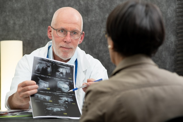 Mature doctor and woman patient looking at xray in medical office