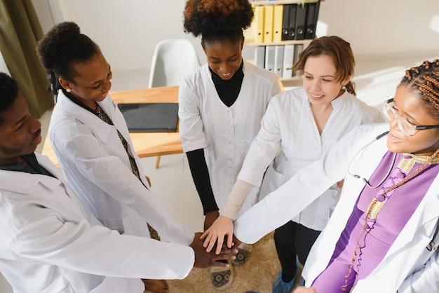 成熟した医師と若い看護師が病院で手を積み重ねています。