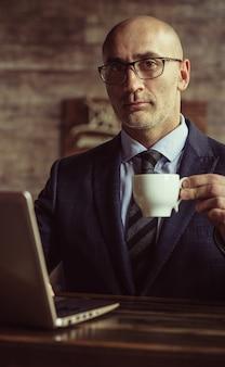 Зрелый элегантный деловой человек в деловом костюме, держа чашку кофе, сидя за столом в то время как