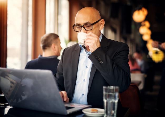 成熟したエレガントなビジネスマンがコーヒーを飲みながらラップトップを使用してコーヒーショップのテーブルに座っています。