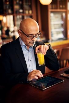 成熟したエレガントなビジネスマンがコーヒーショップでタブレットを使用しているときに、ストローでオレンジジュースを一口飲んでいます。