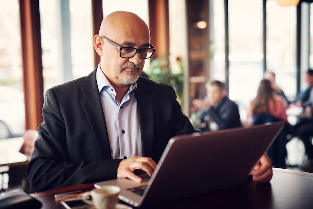 成熟したエレガントなビジネスマンは、コーヒーを飲みながらコーヒーショップのバーに立っている間にラップトップを使用しています。