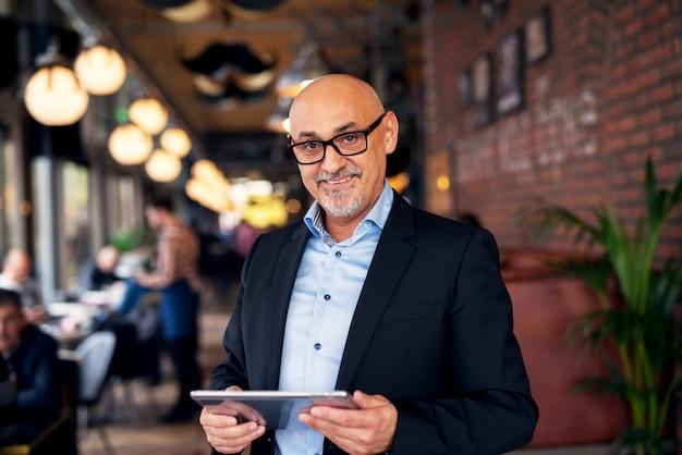 成熟したエレガントな陽気なビジネスマンがコーヒーショップに立っている間タブレットを使用しています。