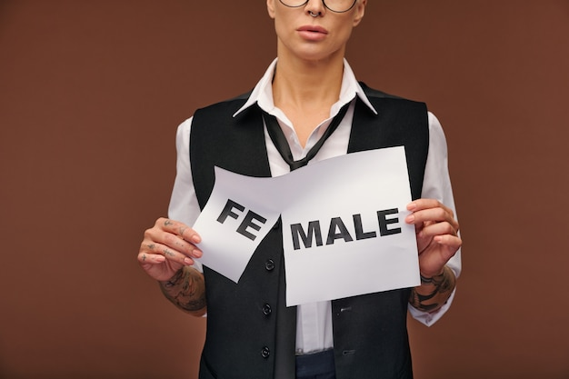 Mature elegant woman in formalwear tearing off syllable fe from word female on paper so that it became male while standing in isolation