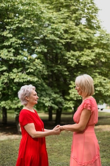 Mature elegant women holding hands