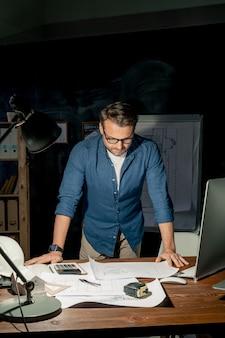 Зрелый инженер наклоняется над столом, глядя на эскиз на бумаге во время сверхурочной работы в ночное время