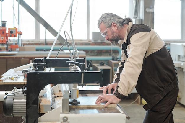 Зрелый инженер мебельной фабрики наклоняется над промышленным станком в мастерской, фиксируя заготовку для дальнейшей обработки