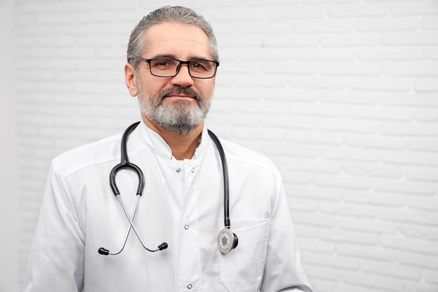 Mature ent doctor posing with stethoscope on neck.