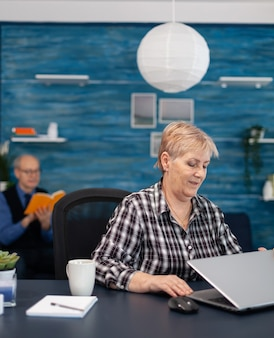 Mature entrepreneur sitting in front of portable computer in office