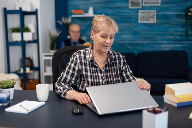 사무실에 있는 휴대용 컴퓨터 앞에 앉아 있는 성숙한 기업가. 집 거실에 있는 노부인은 실내 책상에 앉아 의사 소통을 위해 모더 테크놀로이 노트북을 사용합니다.