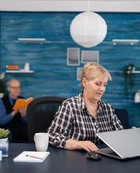 사무실의 휴대용 컴퓨터 앞에 앉아 있는 성숙한 기업가 무료 사진