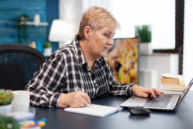 Mature entrepreneur taking notes on notebook working in home office