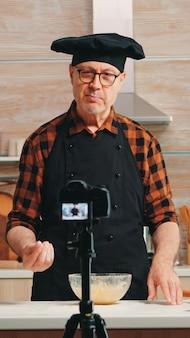 ソーシャルメディアの視聴者記録チュートリアルのレシピを説明する成熟した経験豊富なパン屋。インターネット技術を使用して通信し、デジタル機器で撮影する引退したブロガーシェフのインフルエンサー