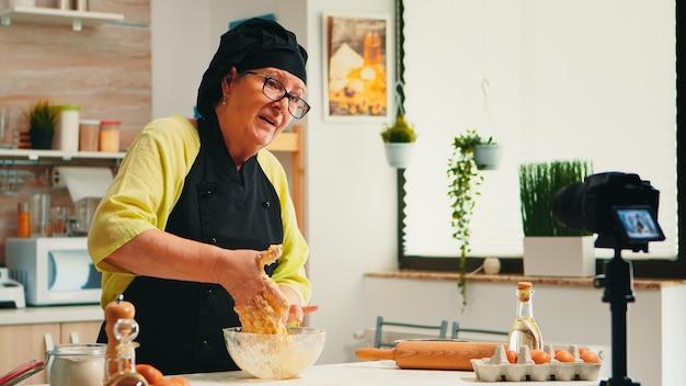 成熟した経験豊富なパン屋が、ボーンテとエプロンを身に着けたキッチンで最新のカメラを使用して料理レシピのチュートリアルを記録しています。ソーシャルメディアで通信するインターネット技術を使用するインフルエンサーシェフ。