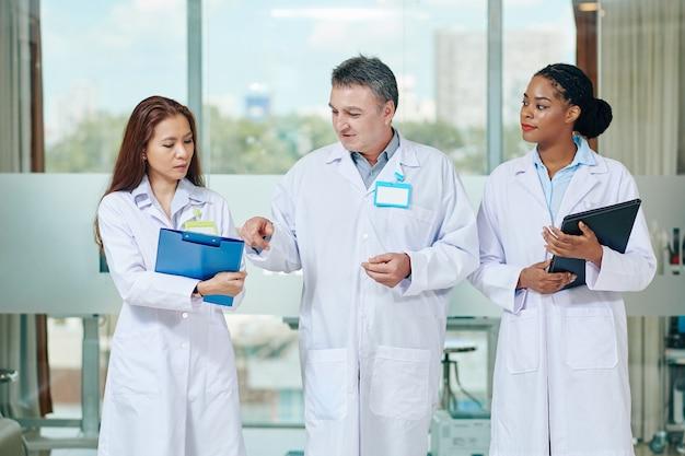 病院のホールを歩いているときに診断を下すためにインターンを助ける成熟した経験豊富な医師