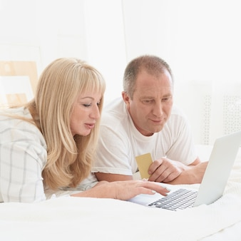 Mature family couple looking at laptop screen. happy middle aged man holding credit card