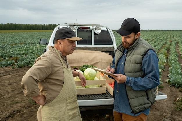Зрелый фермер разговаривает с молодым бородатым мужчиной с документом