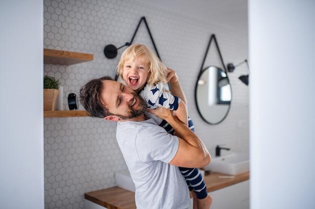 성숙한 아버지는 욕실에서 작은 아들을 안고 즐겁게 놀고 있습니다.
