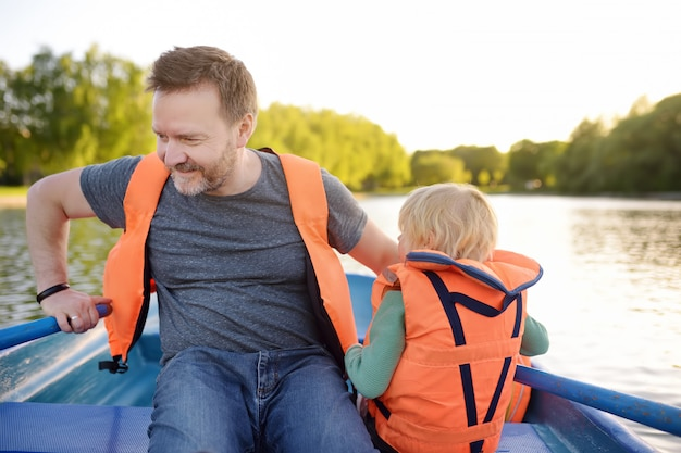 Mature father and little son boating on a river or pond at sunny summer day.