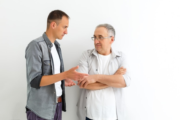 Mature father and son, quarrel, isolated on white wall