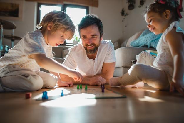 Зрелый отец с двумя маленькими детьми отдыхает в помещении дома, играя в настольные игры