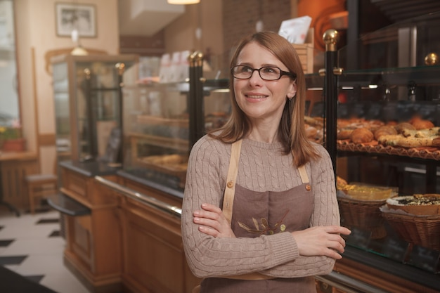 Mature female baker looking away dreamily, working at her bakery shop