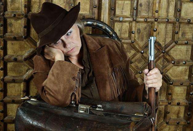 서부에서 총을 든 성숙한 여성 산적
