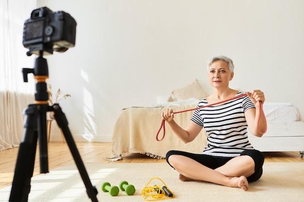 Blogger femmina matura seduta sul pavimento con manubri e corda per saltare, registrazione video per il suo blog, tenendo la fascia elastica, guardando su treppiede, spiegando come utilizzare attrezzature sportive