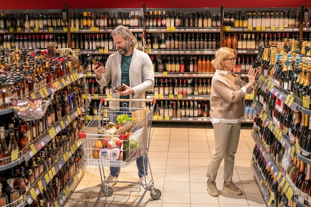 Mature female consumer choosing bottle of champagne while her husband with shopping cart going to buy cognac in supermarket