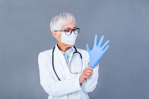 Mature female doctor putting on protective gloves and medical protective mask