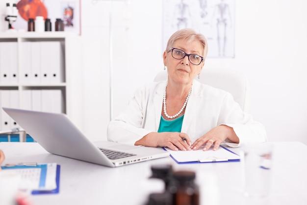 Medico femminile maturo che indossa camice da laboratorio nella stanza di ospedale durante l'utilizzo di laptop. medico che utilizza il taccuino nel posto di lavoro della clinica, fiducioso, competenza, medicina.